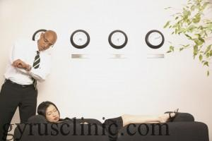 Young businessman standing over a young businesswoman sleeping on a couch --- Image by © Royalty-Free/Corbis