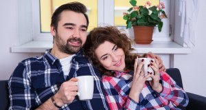 happy young couple sitting on sofa with cups of tea or coffee